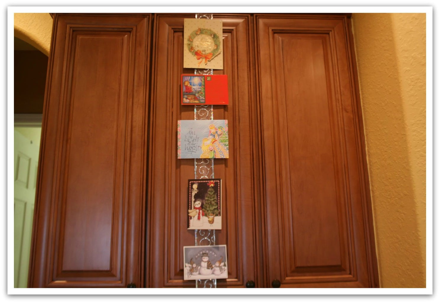 Looking for a way to beautifully display your Christmas cards? I decided to place them on my kitchen cabinets to enjoy as long as I can! This is an easy DIY project!