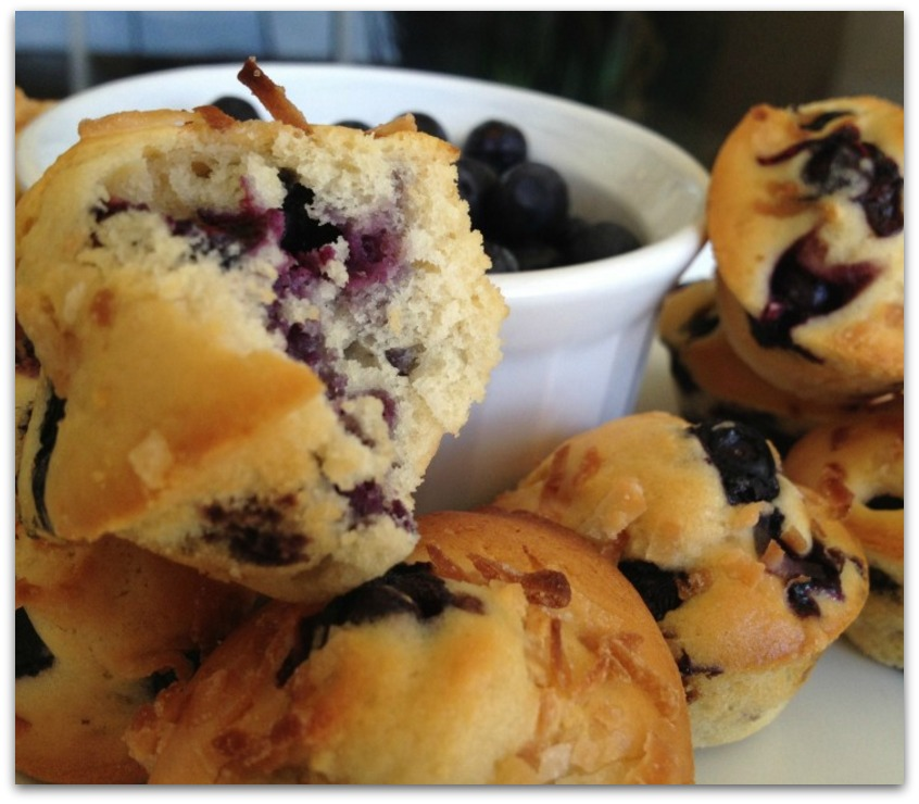 blueberry muffins with a bowl of blueberries