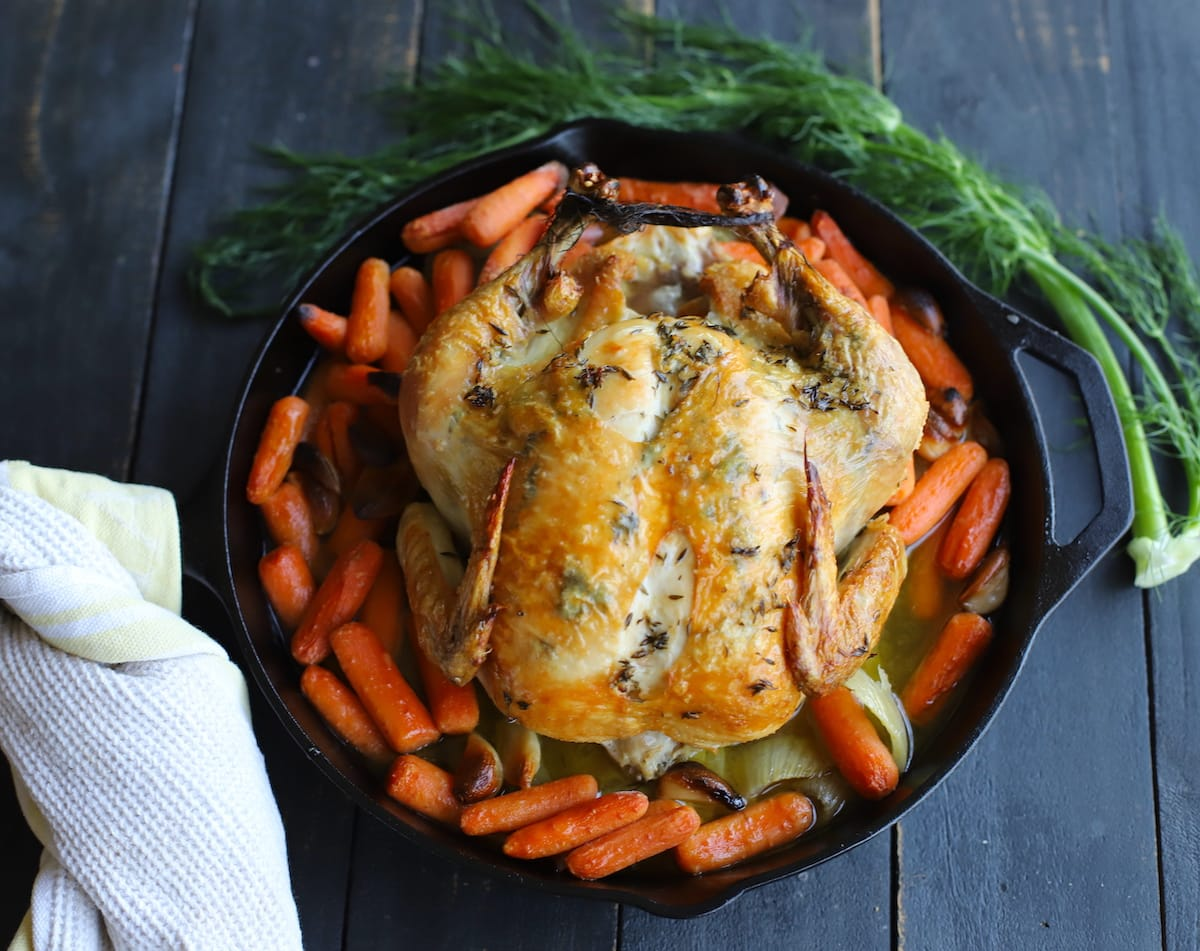 roasted chicken with vegetables in cast iron skillet with fennel fronds