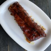ribs glazed with Guinness beer sauce on a white plate on a black board