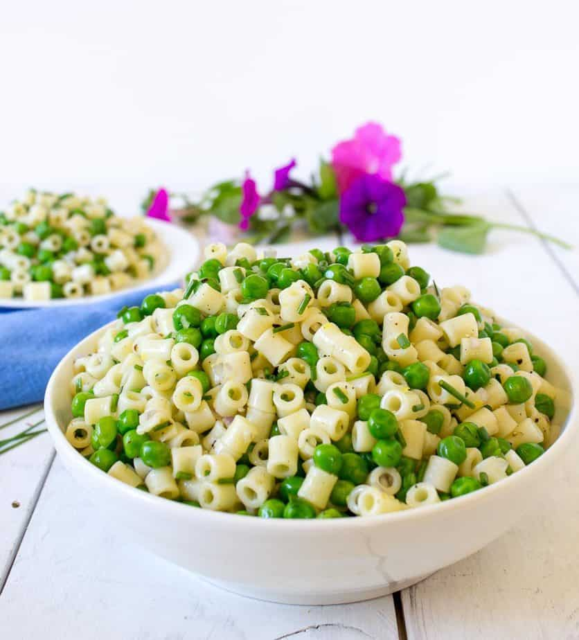 pasta and peas in white bowl in white table