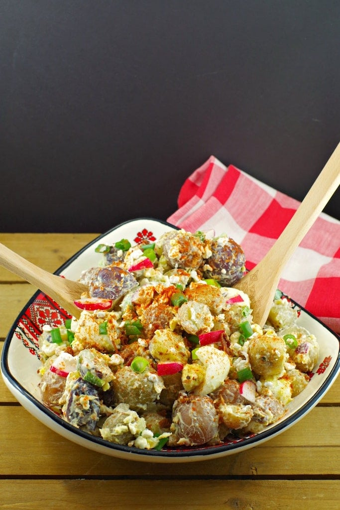 potato salad in a bowl with wooden serving spoons and red plaid napkin