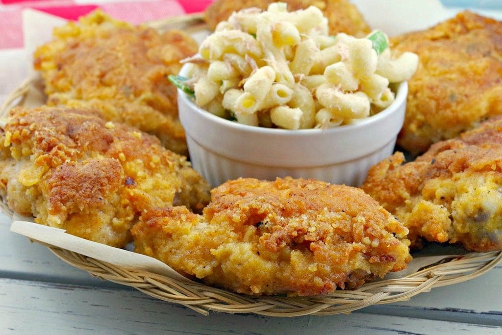 fried chicken on a wicker plate with macaroni salad
