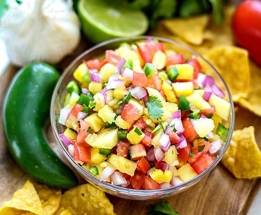 Pineapple, onion, tomato, cilantro in a glass bowl with limes, garlic, and peppers in backgrouns