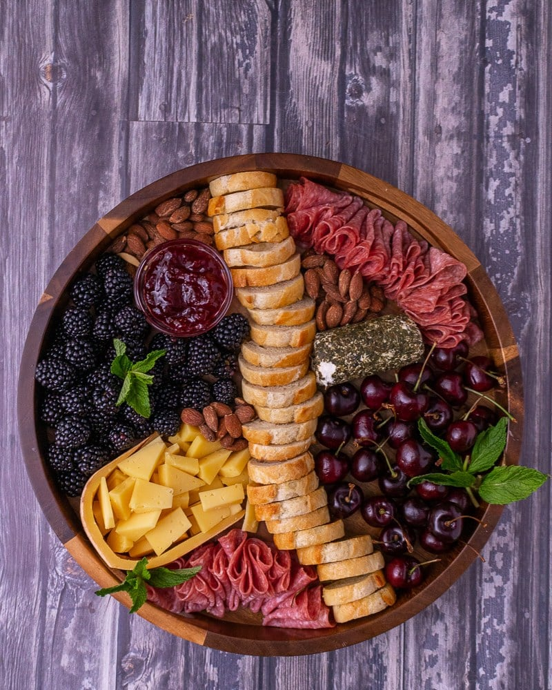 cheeses, meat, olives, grapes, nuts on a wooden platter on a wood table