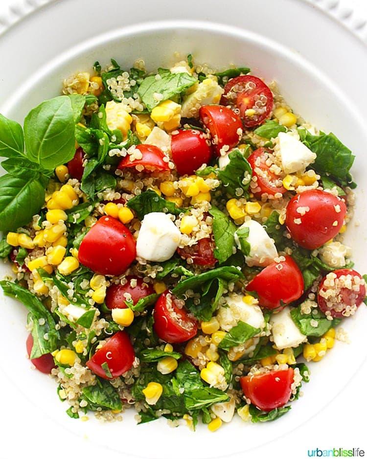 corn, tomato, basil, cheese salad in a white bowl