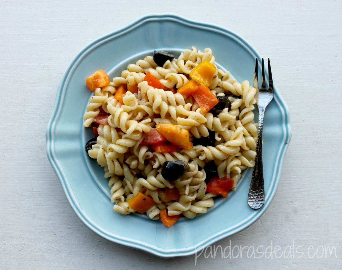 pasta salad with peppers and olives on light blue plate