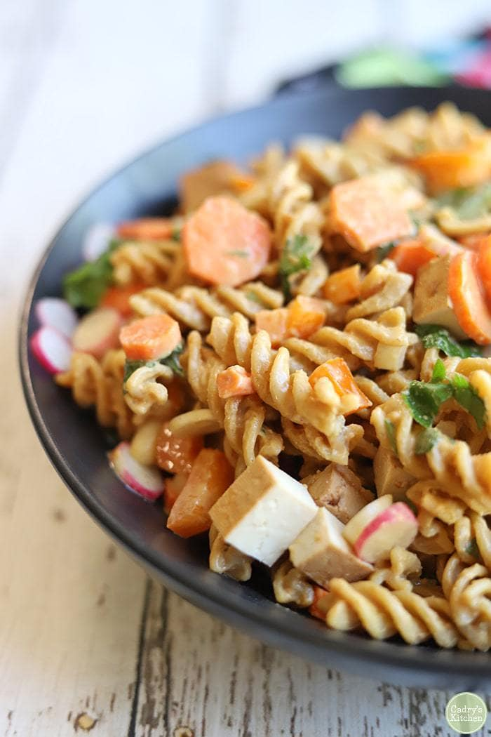 spiral pasta with feta, carrots, radishes in black bowl