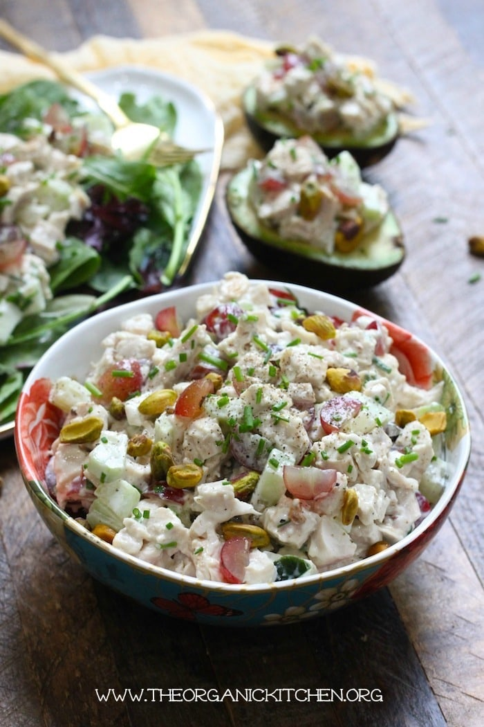 chicken salad in a white and red bowl on a wood table