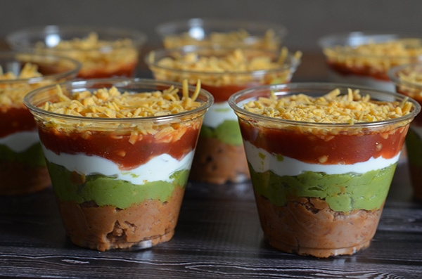 six layer taco dip in a clear cup