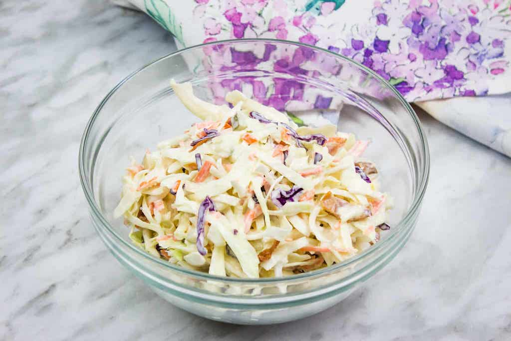 cabbage, carrots, and mayo in a glass bowl