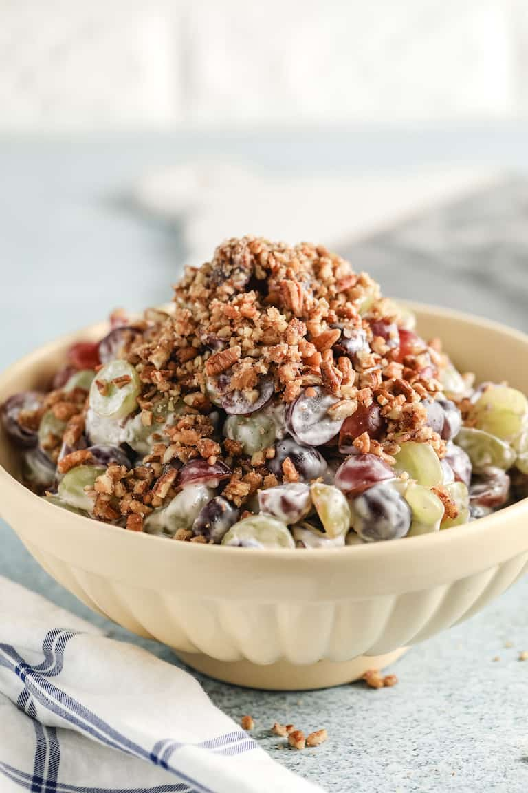 grape salad with mayo and nuts in a tan bowl