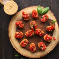 tomato mixture on bread slices on wood plank with salt container on black table