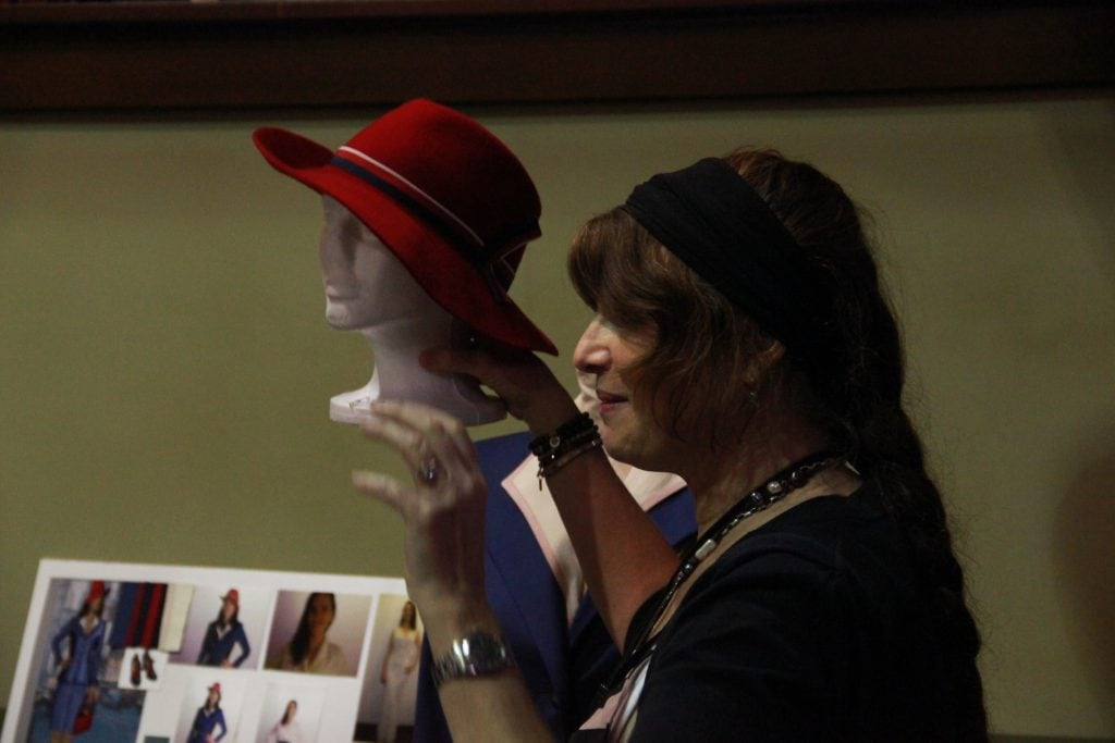 Gigi Melton is the designer behind the fabulous fashion on Agent Carter. Here she holds an idea board showing how she comes up with ideas for what Hayley Atwell and the rest of the cast will wear. In this photo Gigi Melton holds red hat.