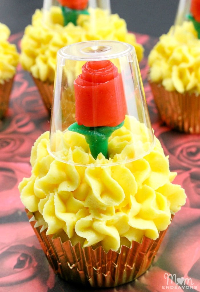 yellow frosted cupcakes with red rose under glass