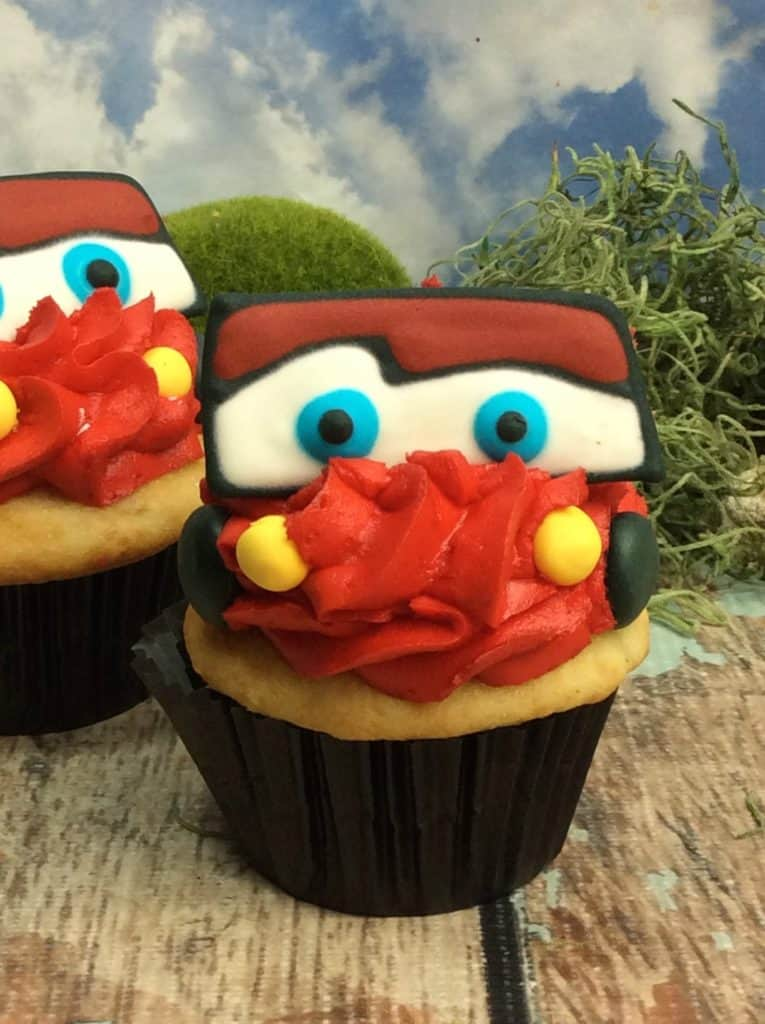 red, white, yellow, blue cupcakes with the face of a car