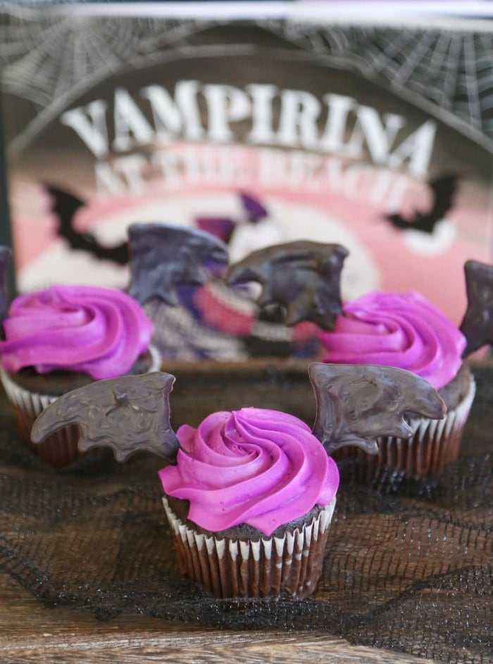 purple and black cupcakes with Vampirina sign in background