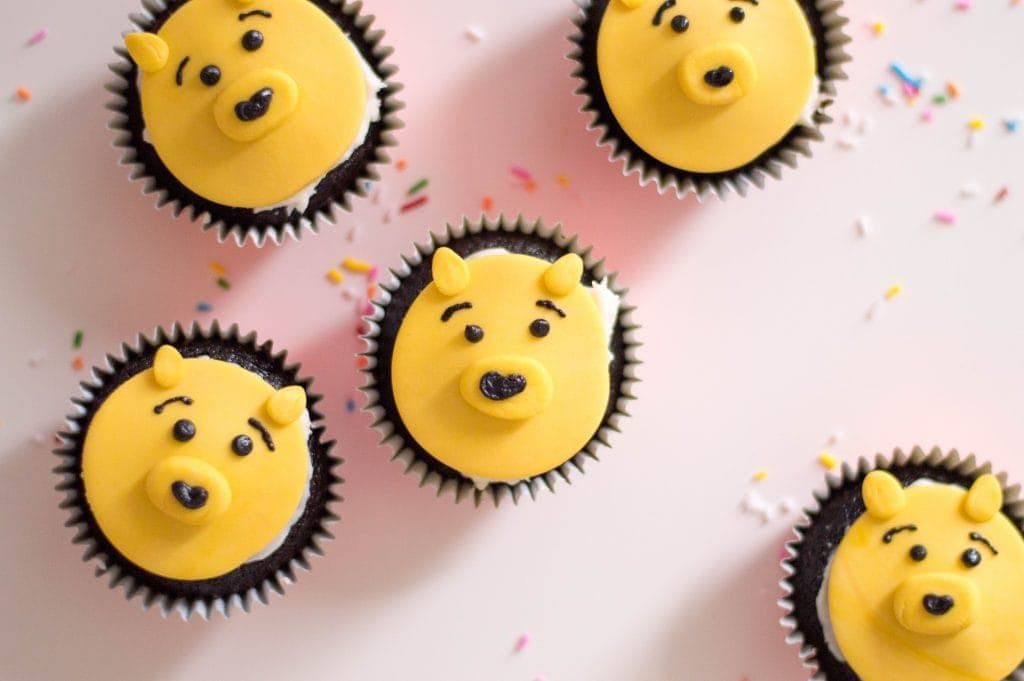 Winnie the Pooh cupcakes on a light pink board