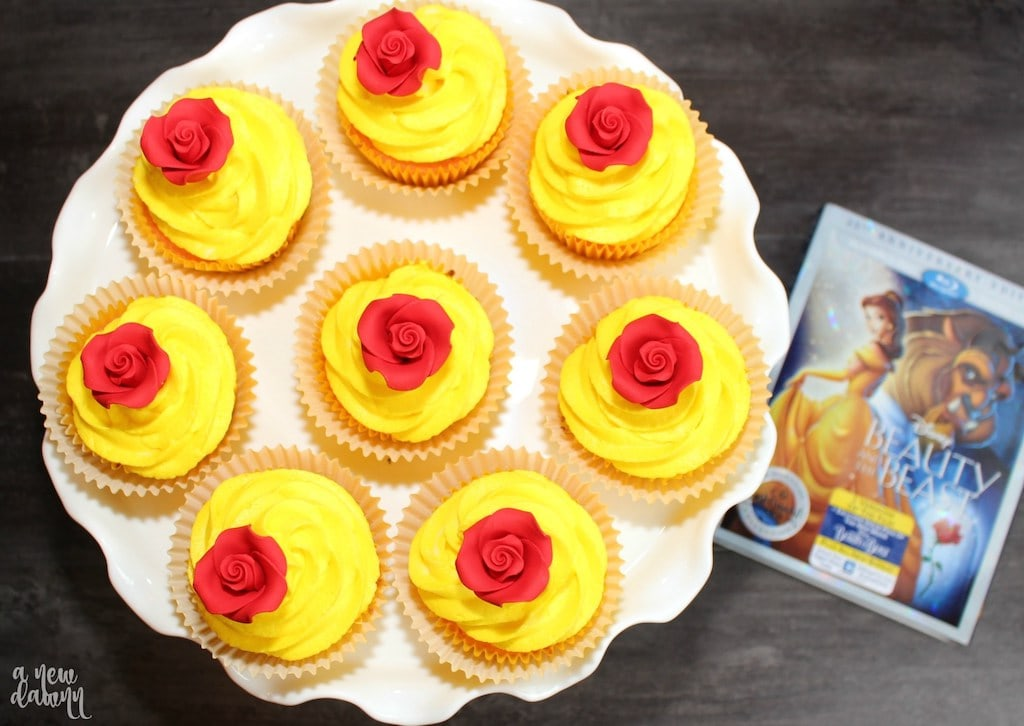 cupcakes with yellow frosting and red rose on top