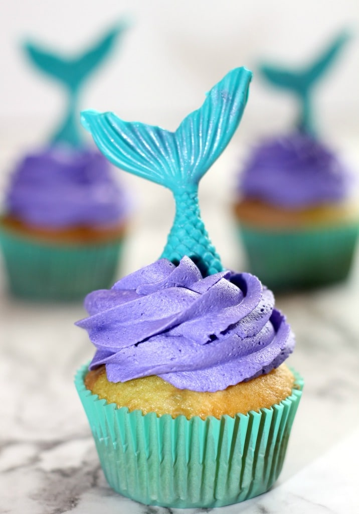 purple cupcakes with blue mermaid tail on top