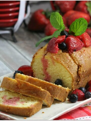Loaf of pound cake with berries and mint.