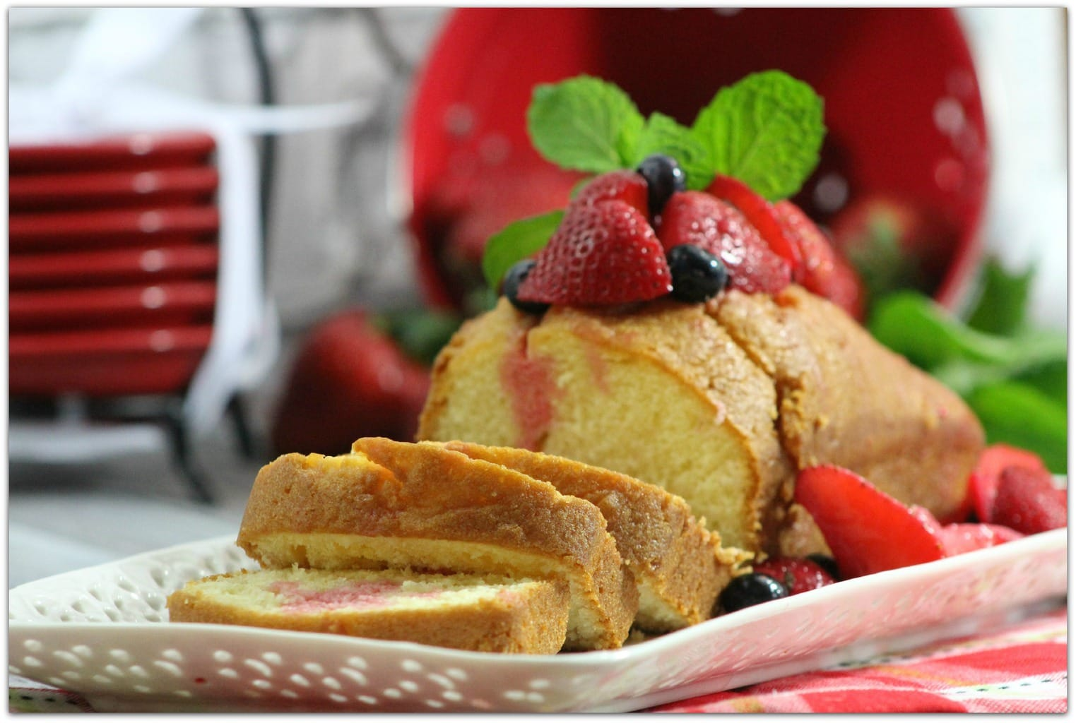 Pound cake with berries and mint on white plate.