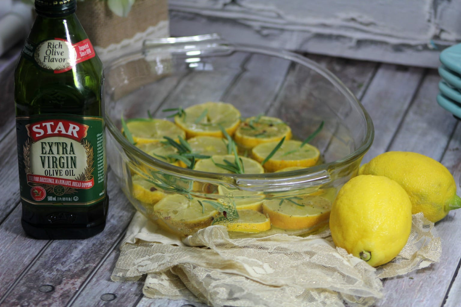 Lemons with rosemary and seasoning in a glass bowl with lemons and olive oil on side.