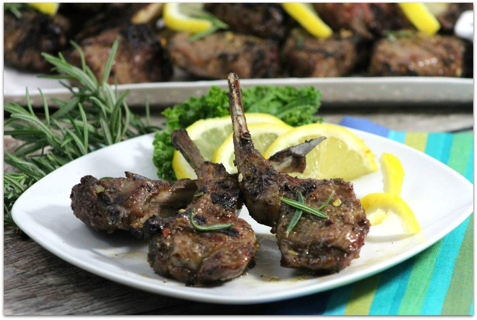 Lamb chops grilled on a white plate with lemons.