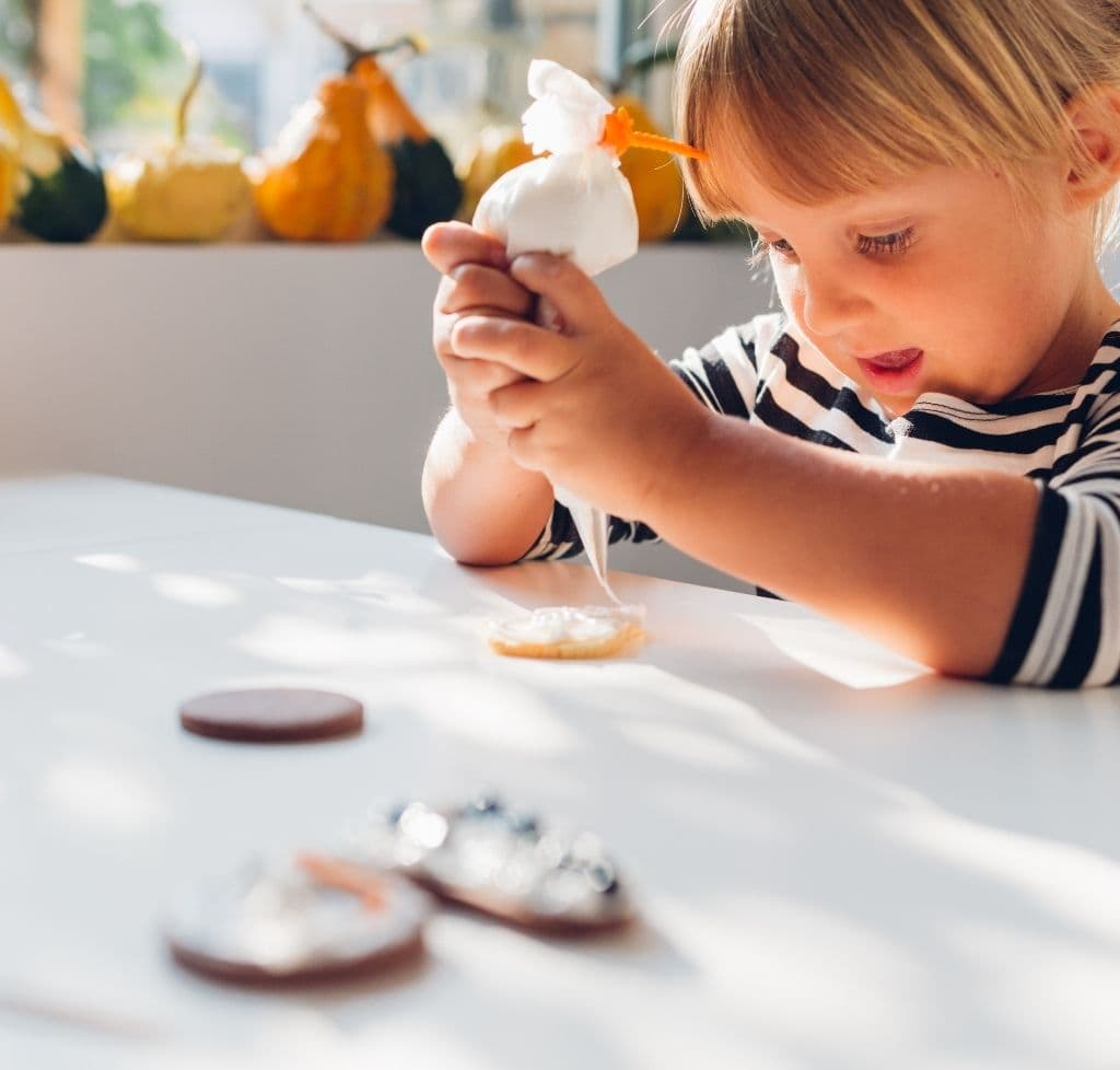 young girl decorating cookies on a white table