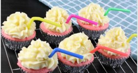 Pink cupcakes with yellow icing and a straw on a wire rack.