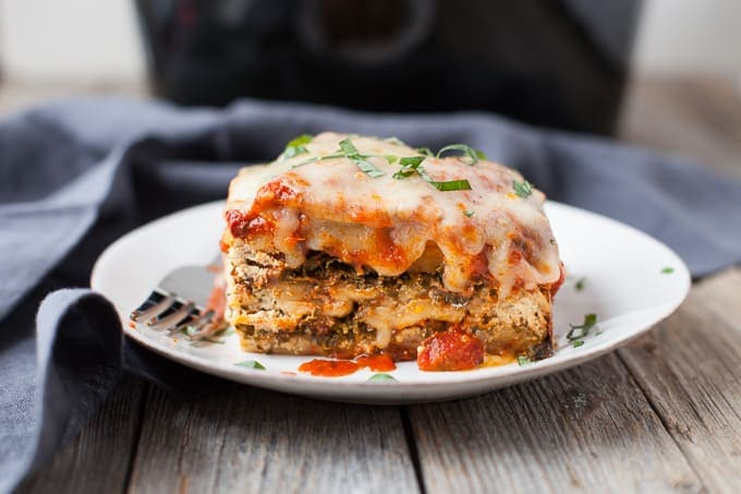lasagna on a white plate on an off white board