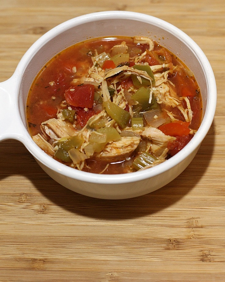 chicken in a red broth with tomatoes and vegetables