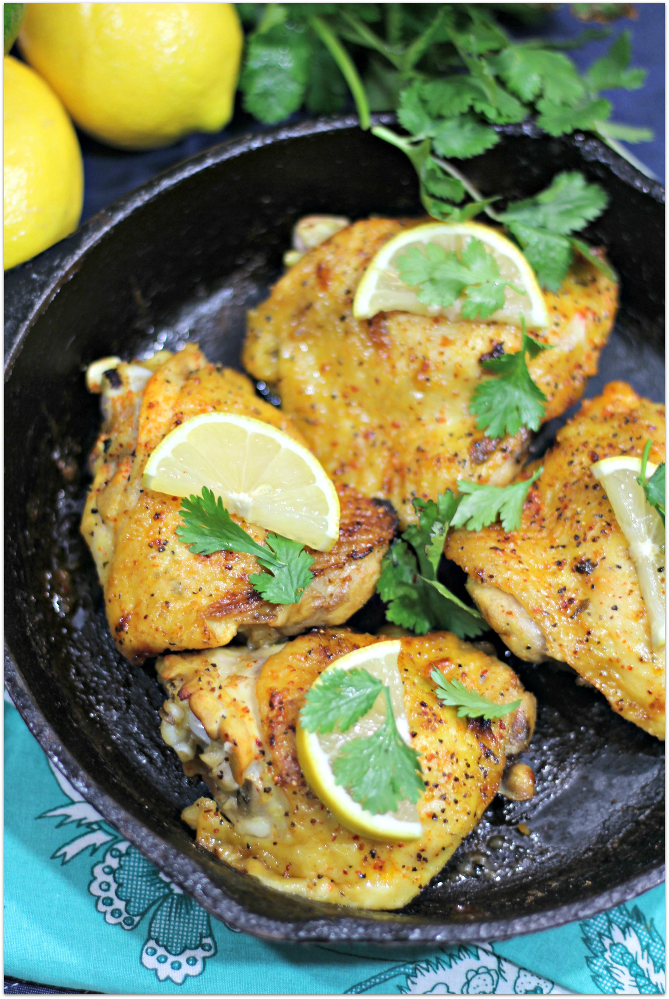 chicken with cilantro and lemon in cast iron skillet.