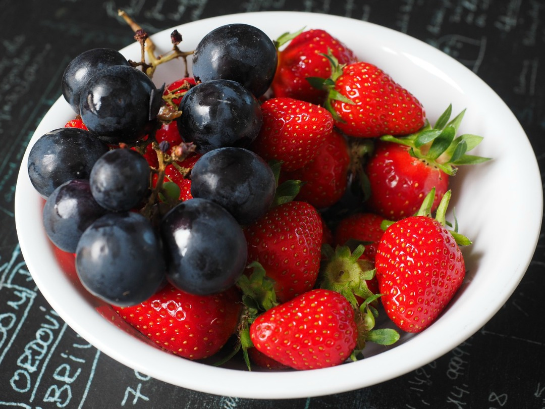 Strawberries and blueberries in a white bowl.