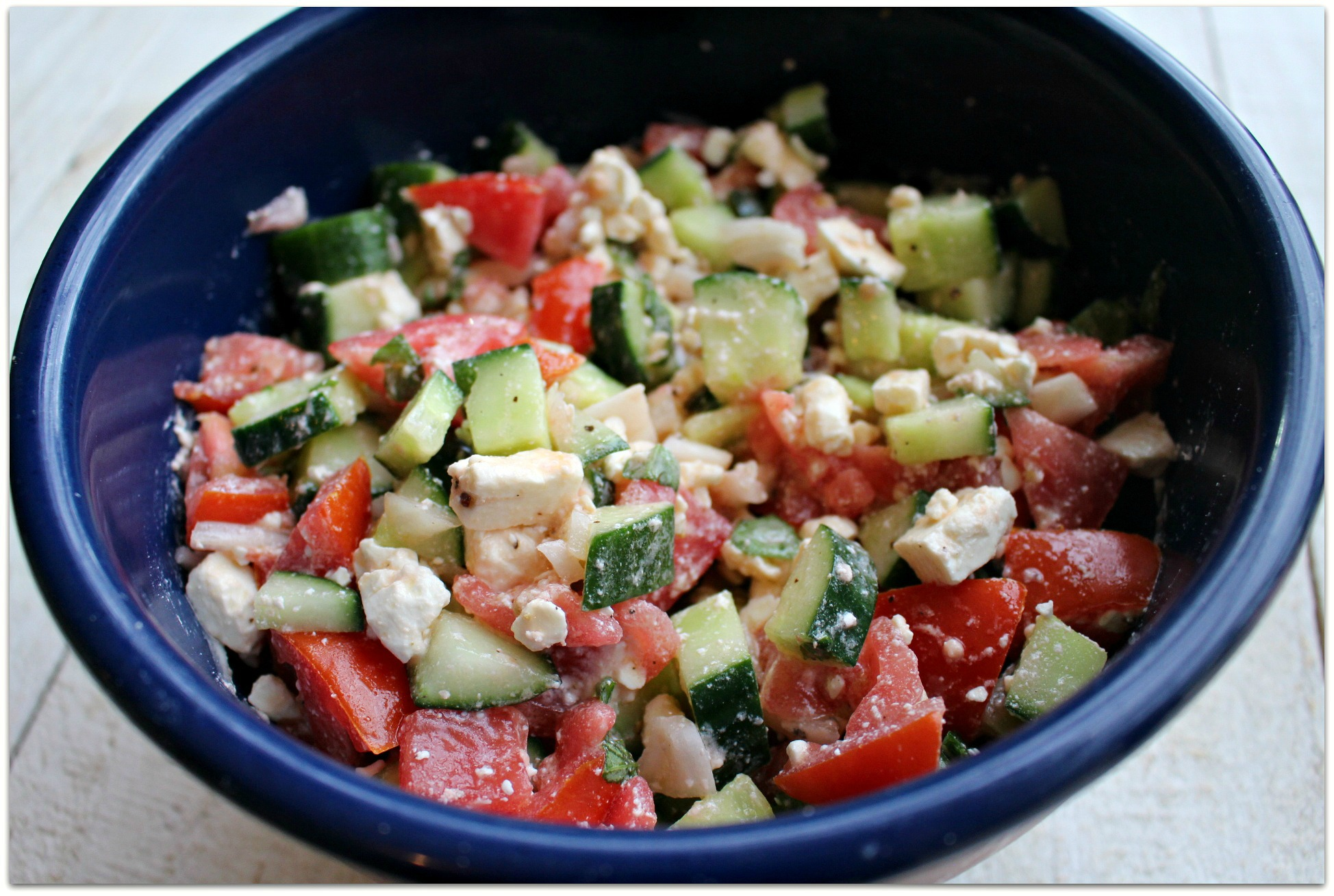 cucumber and tomato salad with feta in a blue bowl