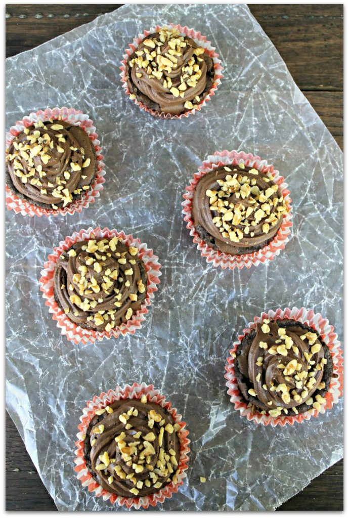 Preheat oven to 350. Prepare the brownie mix according to directions, but add an extra egg and ¼ cup more oil. Add in your banana, chocolate chips and ½ of the nuts. In a muffin tin, line with cupcake liners or spray with vegetable oil. Fill ⅔ full. Bake for 22-25 minutes or until a toothpick comes out clean. Frost your cupcakes and sprinkle remaining walnuts.
