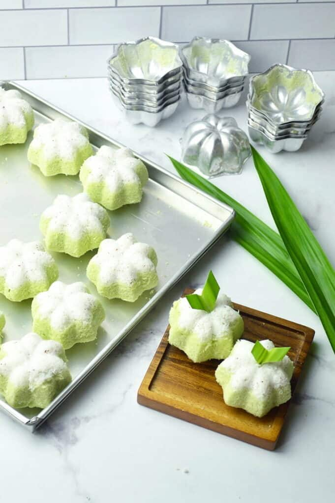 Small green flower shaped cakes on a baking sheet.