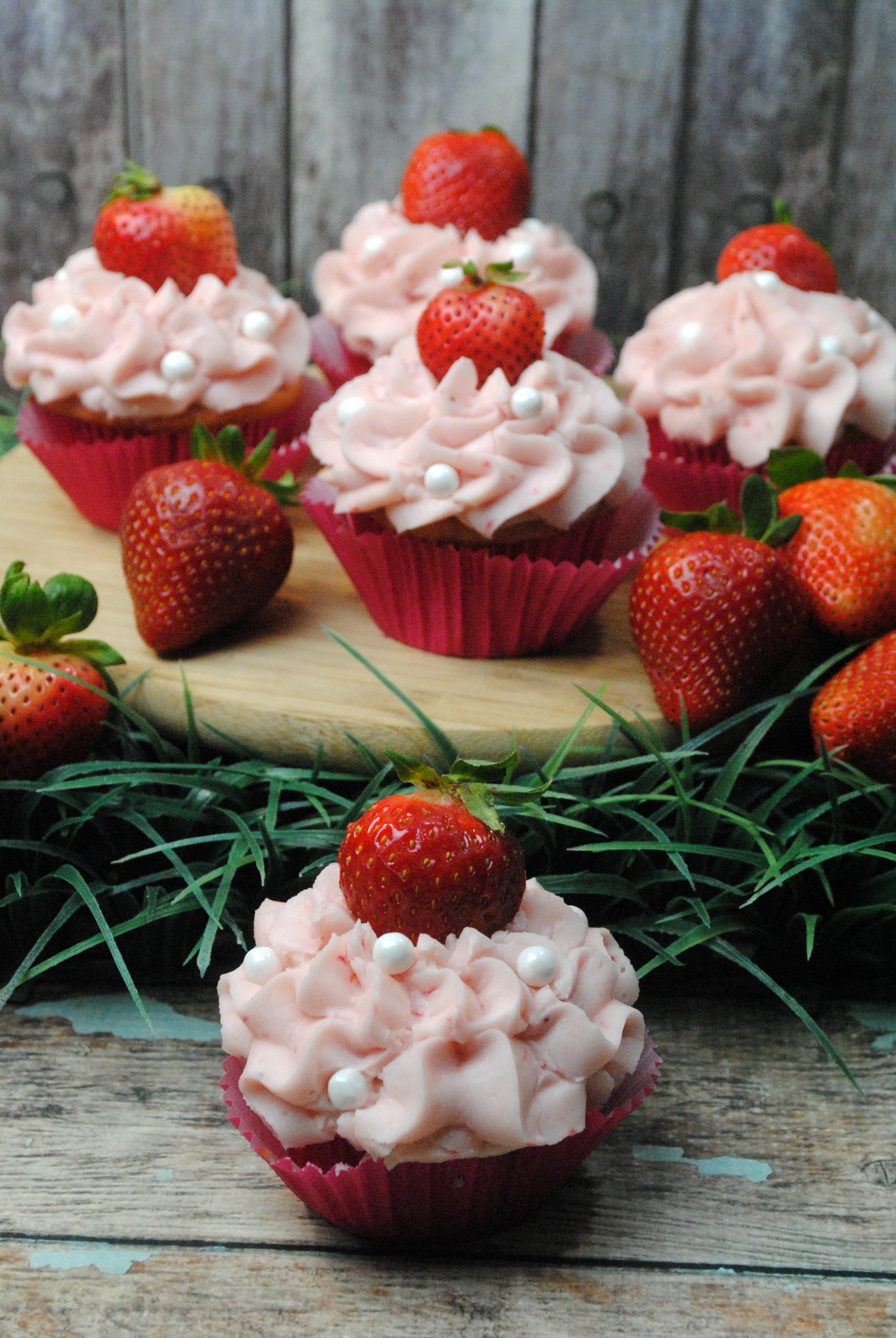 strawberry cupcakes on a wood board with grass