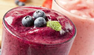 Purple smoothie with blueberries and mint on top.