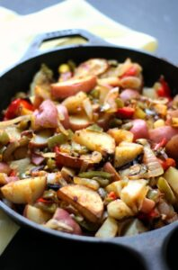 Potatoes with onions and peppers in a skillet.
