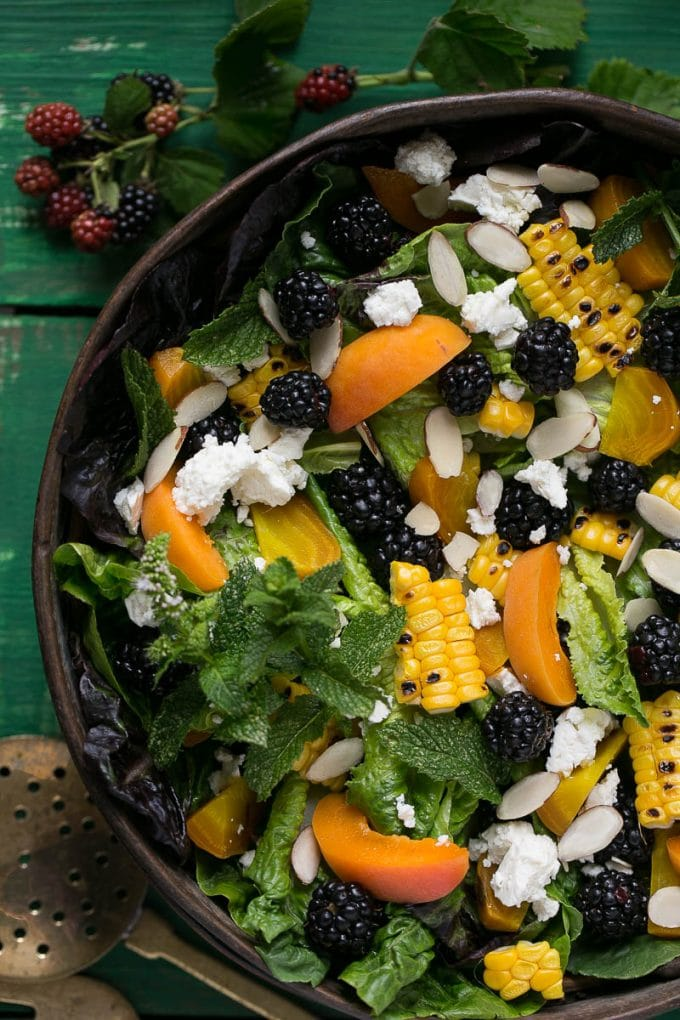 blackberry salad with corn and feta in a bowl on a green board