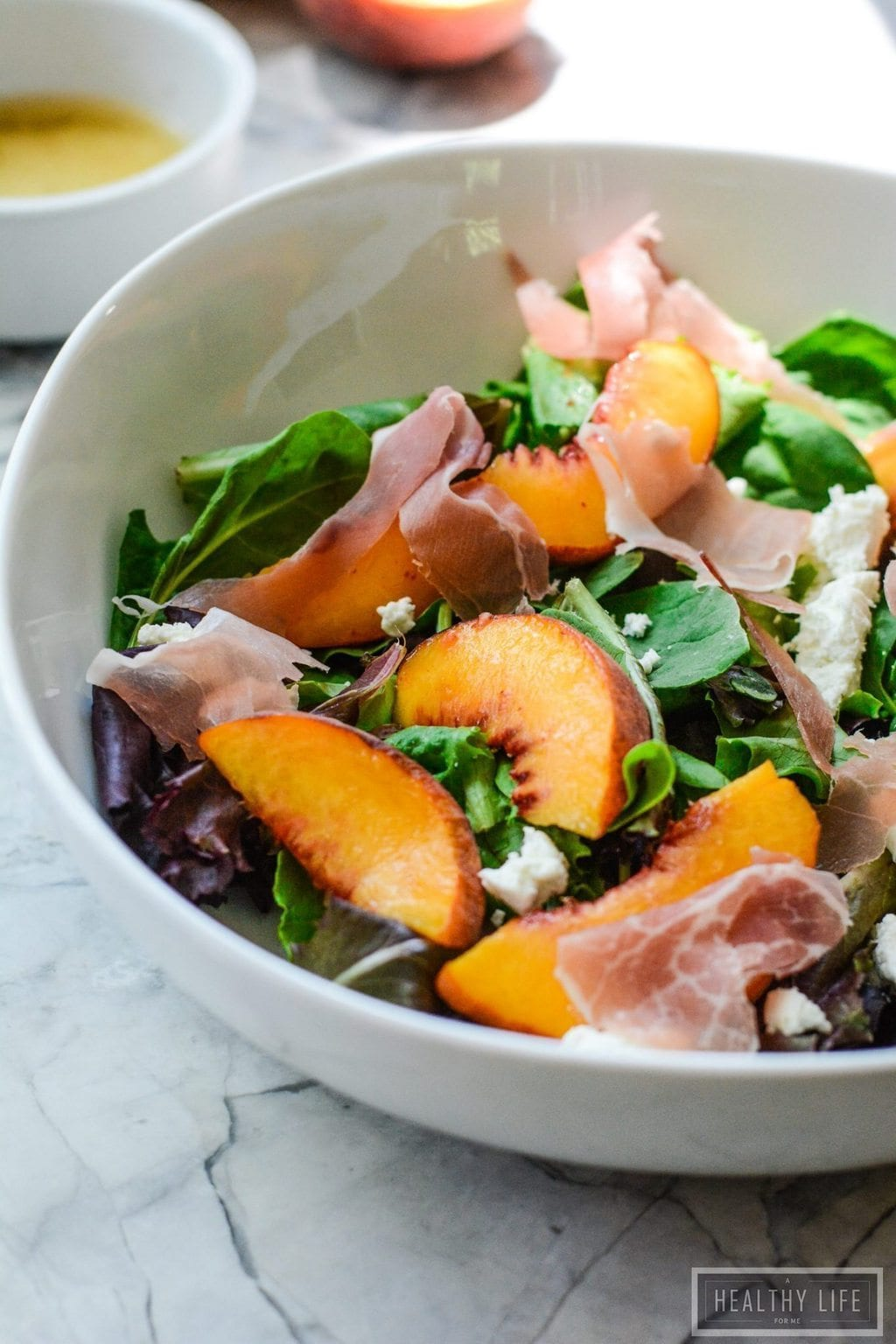 peach prosciutto salad in a white bowl
