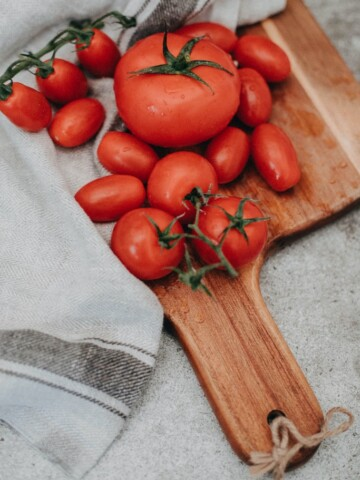 tomatoes on chopping board with towel