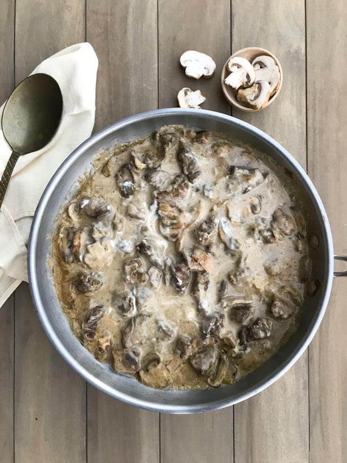 beef stroganoff in stainless pan with spoon on a wood board
