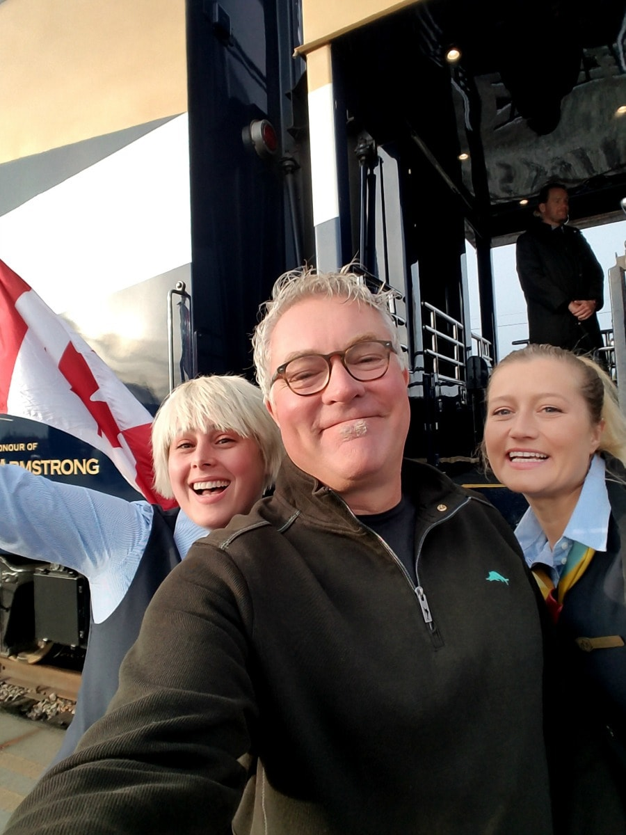 Man with Rocky Mountaineer Train staff with train in background.