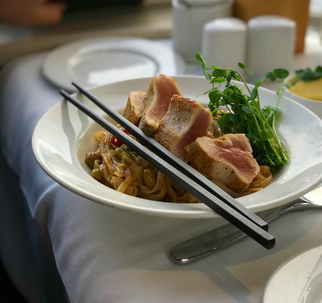 Seared tuna over noodles with chopsticks in a white bowl.