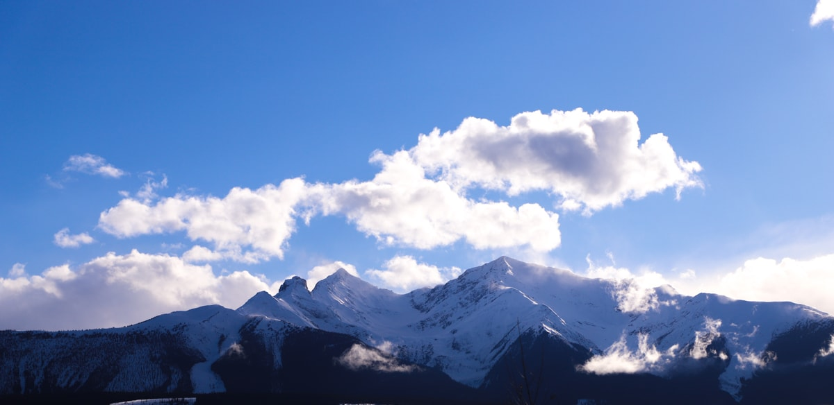 Snow covered mountains and blue sky with white clouds.
