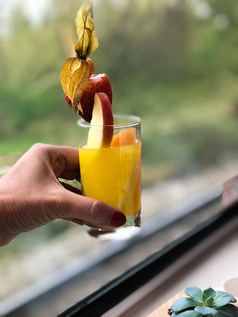 Glass of juice in front of window on Rocky Mountaineer Train.