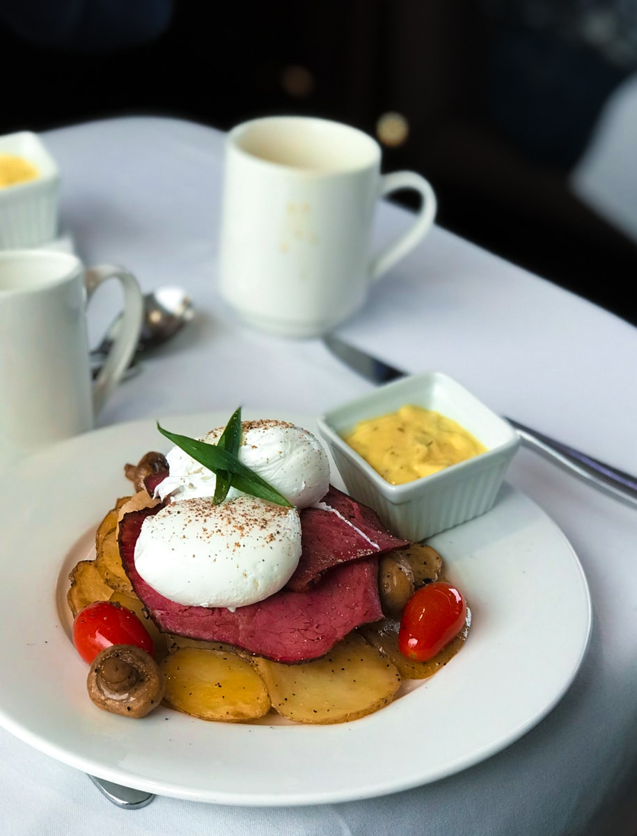 Eggs, ham, potatoes, and tomatoes on a white plate with coffee cup in background.