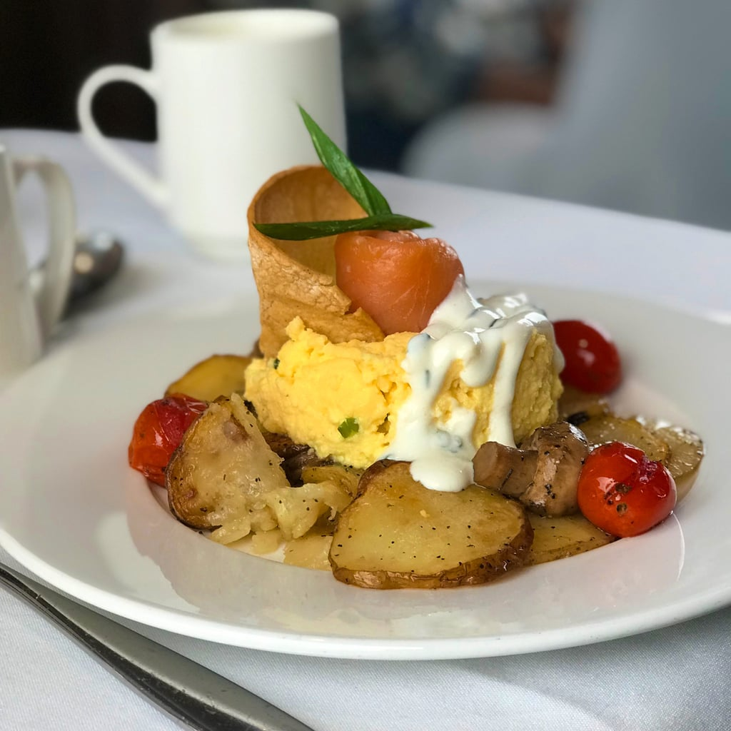 Eggs, potatoes, tomatoes, and creme fraiche on white plate on white tablecloth with coffee cup in background